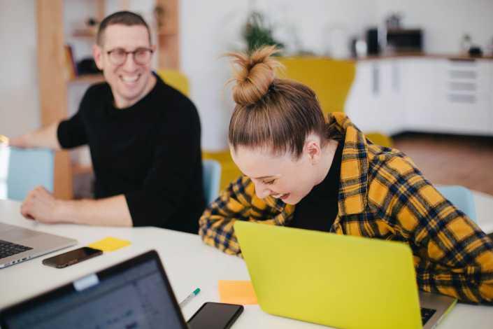 Två personer samtalar och skrattar vid varsin dator