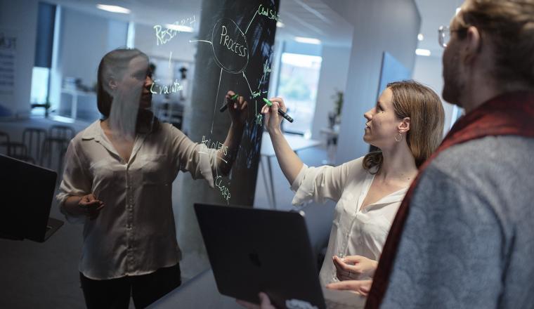 Man och kvinna pekar på projekttavla vid glasvägg